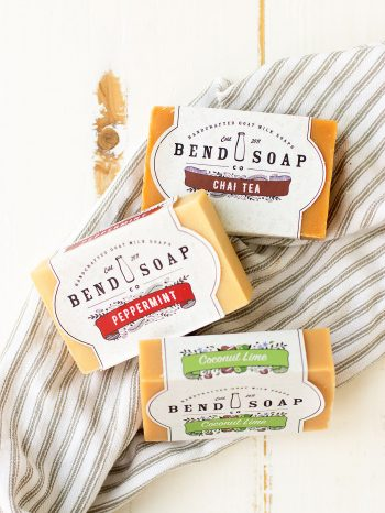 Goat milk soap benefits your skin. Bend Soap is the company that I always choose. Three bars from the company are laid out on a cloth.