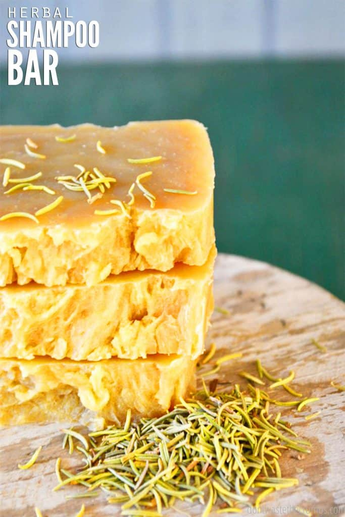 Three bars of homemade soap, with uneven edges, are stacked on top of one another and sprinkled with rosemary.