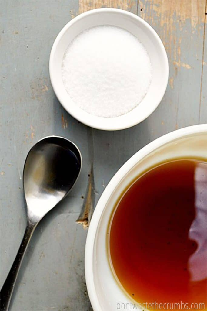 A bowl of herbal water soaks in a white bowl. A metal spoon rests next to the bowl.