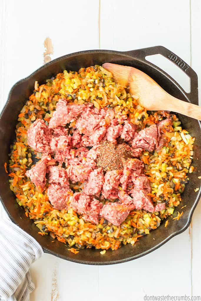 Chunks of raw ground meat and seasoning sit atop cooked vegetables.