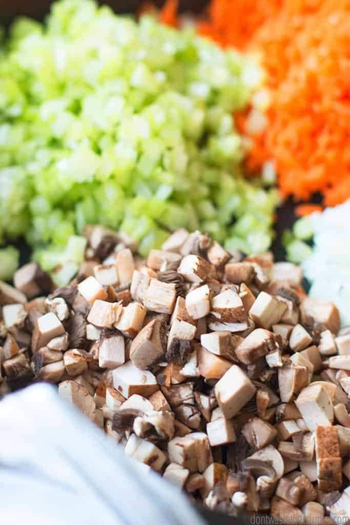 A board is covered with chopped green peppers, shredded carrots, finely chopped onion, and chopped mushroom.