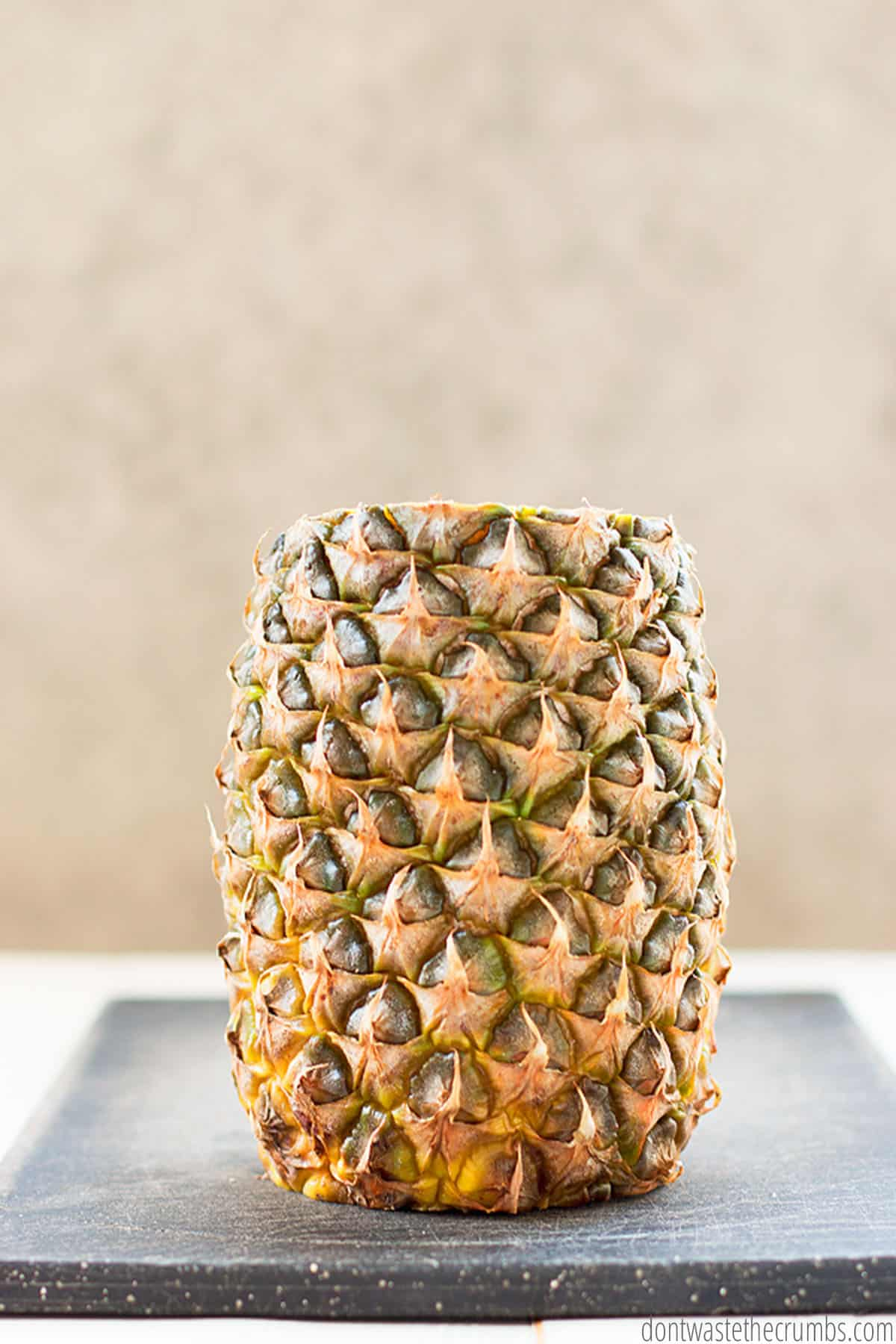 Here is a whole pineapple with the leafy  tops and the bottom cut off.