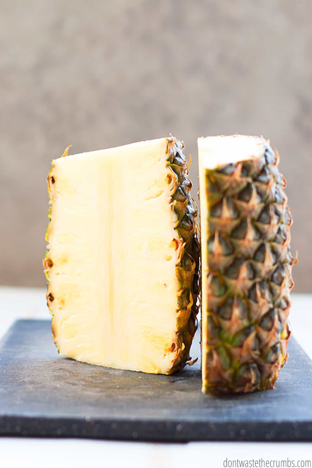 A whole pineapple cut in half with the skin on and the top and bottom and cut off.