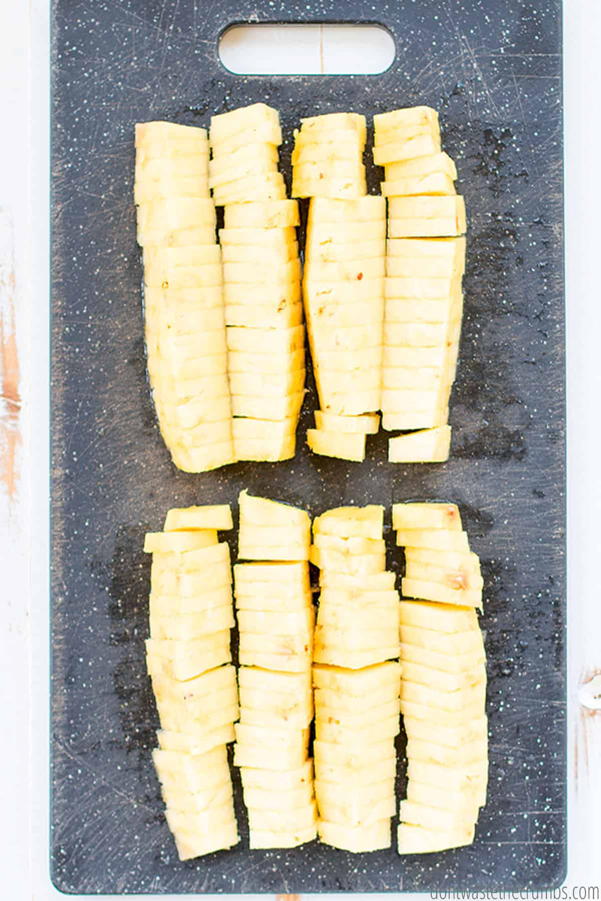 Many slices of freshly cut pineapple on a cutting board. Ready to serve and eat!