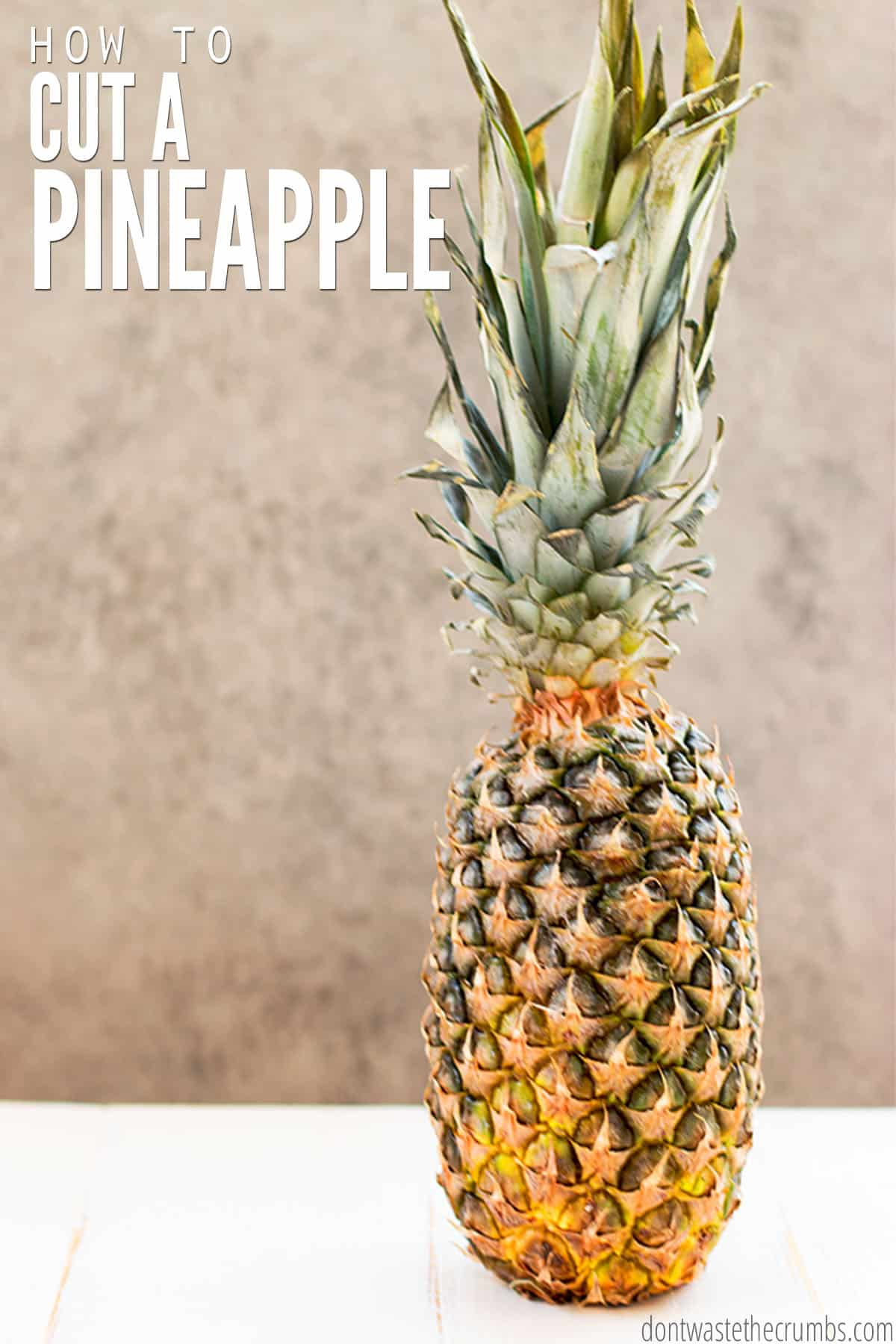 """A fresh whole pineapple with the leaves. The text overlay reads, """"How to cut a pineapple."""""""