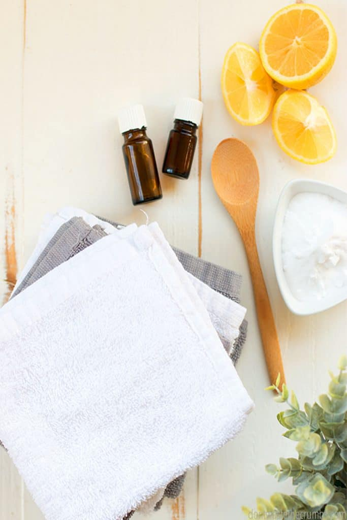 A pile of folded towels lie next to a bowl of baking soda, two bottles of essential oils, and lemon.