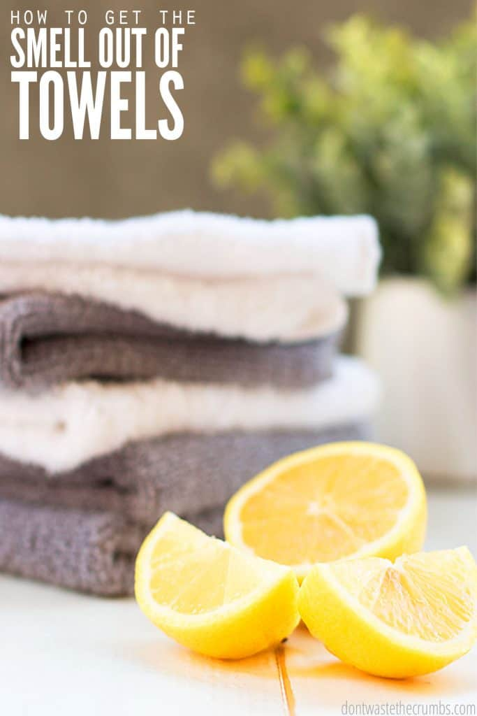 """A stack of white and gray folded towels sit next to a fresh lemon. Text overlay reads """"How to Get the Smell Out of Towels."""""""