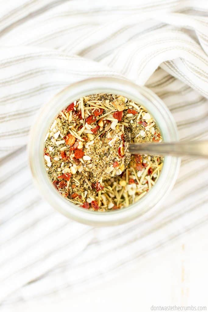 Montreal steak seasoning in a glass jar. A tablespoon scoops the seasoning to be used in a recipe favorite!