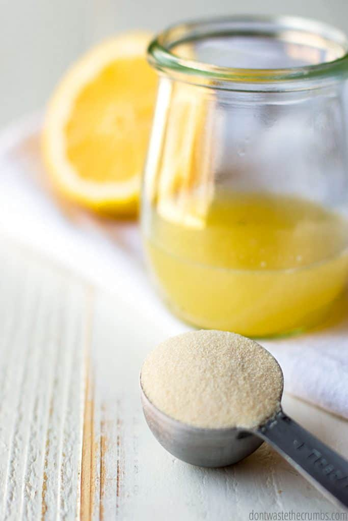 A half lemon sits next to a jar with honey and a tablespoon filled with gelatin.