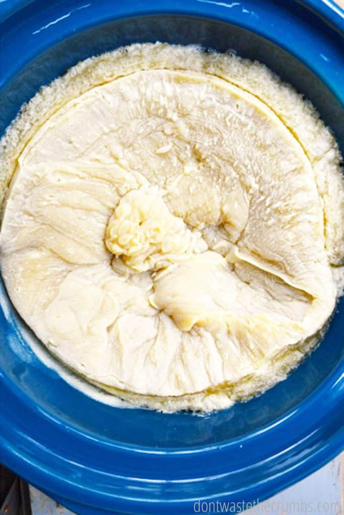 Neutralized soap, its texture thick and lightened to the color of bread dough, rests in a crock pot.