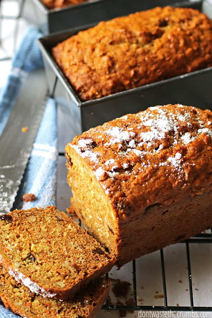 Two slices of carrot bread are cut from the loaf as it rests on a wire rack. Powdered sugar dusts the top.
