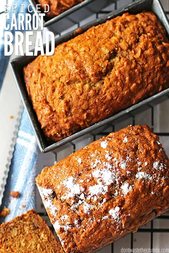 """Two carrot bread loaves, one still in the loaf pan and one dusted with powdered sugar, sit atop a blue and white towel. Text overlay reads """"Spiced Carrot Bread."""""""