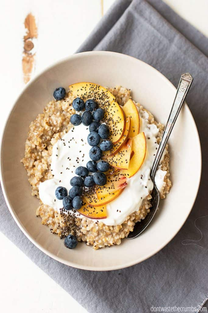 A bowl of cooked steel cut oats is topped generously with yogurt and fresh berries and peaches.