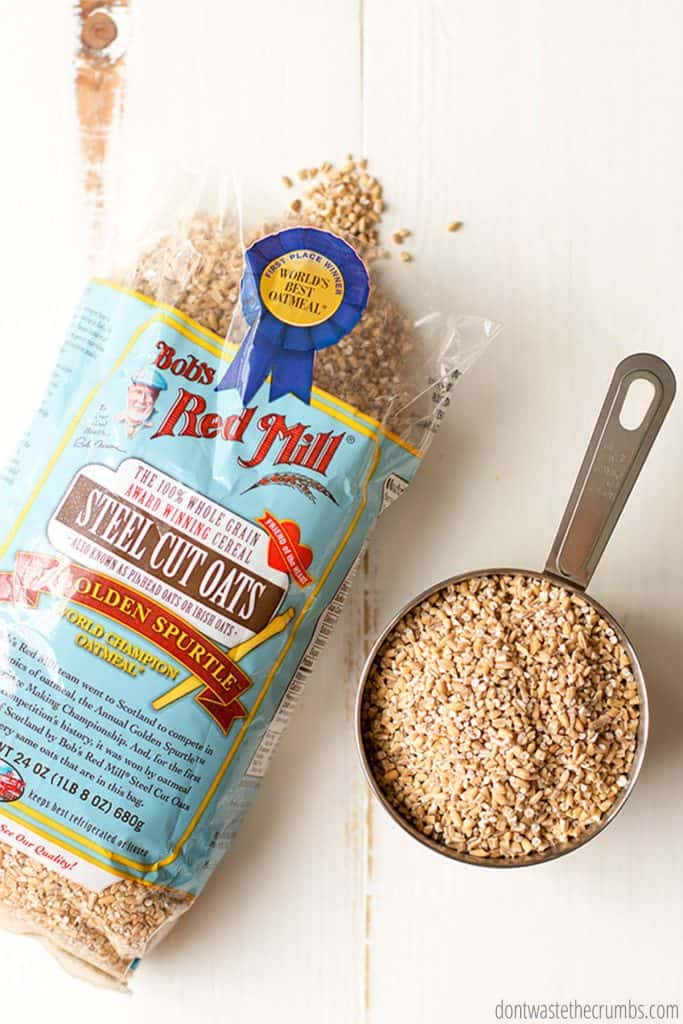 A bag of Bob's Red Mill Steel Cut Oats sits next to a measuring cup filled with oats.