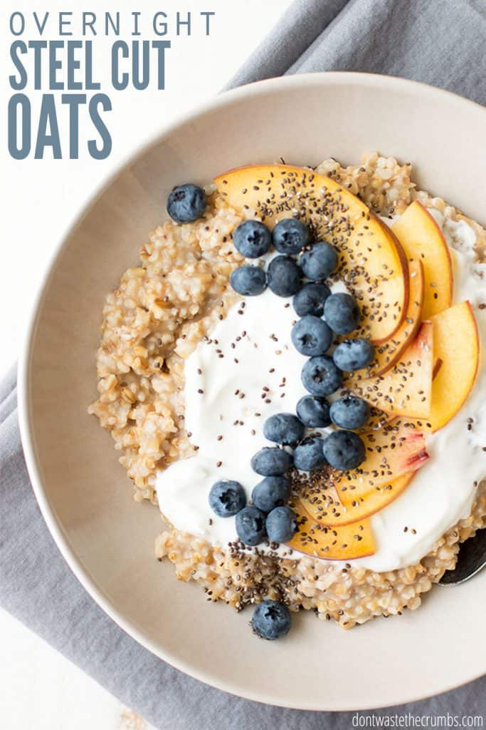 """A bowl of steel cut oats is topped with yogurt, blueberries, and peach slices. Text overlay reads """"Overnight Steel Cut Oats."""""""