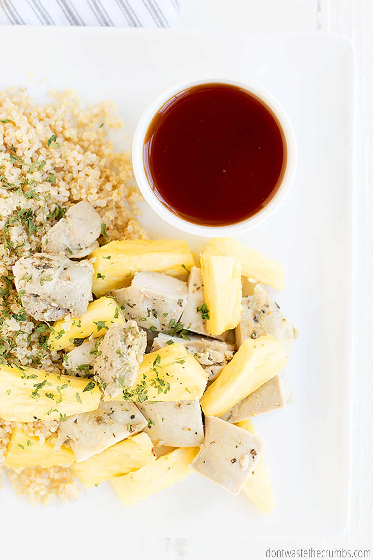 Pineapple chicken over quinoa with a small white bowl of fresh sweet and sour sauce.