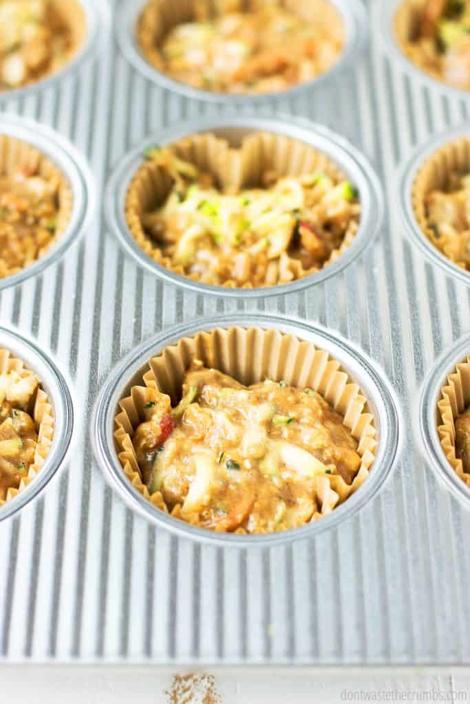 Batter is evenly distributed in muffin cups, with bits of zucchini visible in the batter.