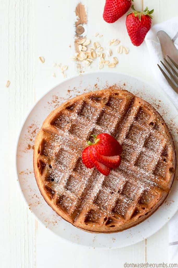 A waffle is dusted with powdered sugar and topped with a sliced strawberry.