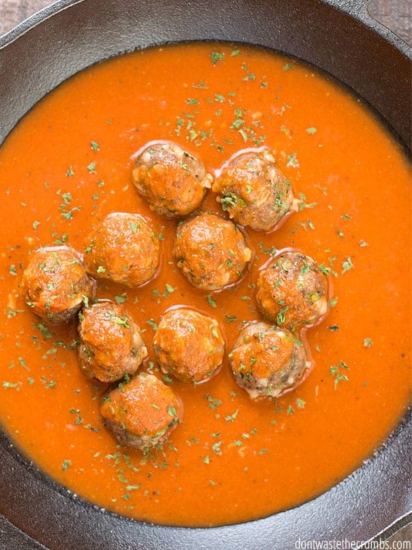 A skillet is filled with rich tomato sauce and meatballs, sprinkled with dried herbs.