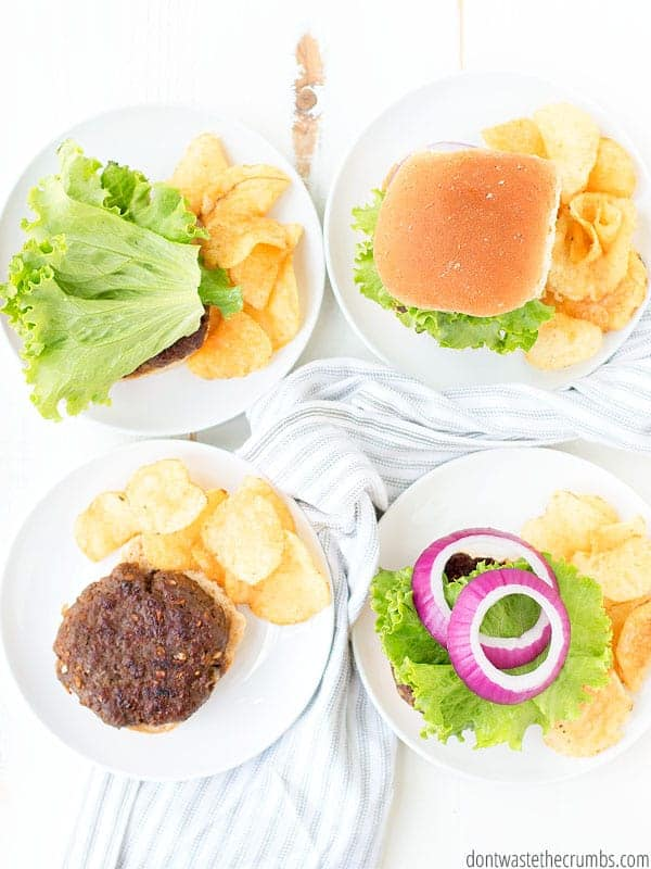 Four burgers are served up on homemade buns with a side of potato chips and topped with lettuce and shredded onion.