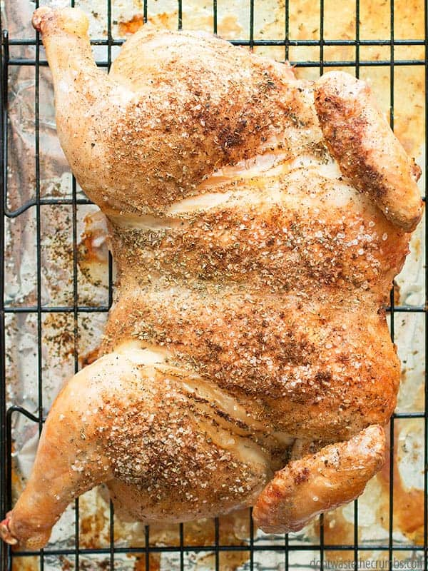 A fully roasted whole chicken rests on a baking rack to cool.