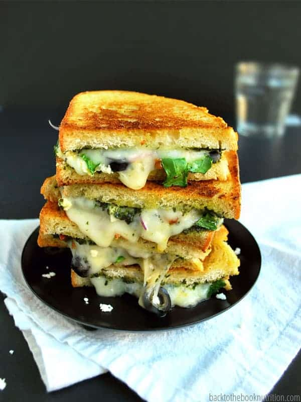 A three-layer grill cheese is melted to perfection and filled with olives, lettuce, and cheese.