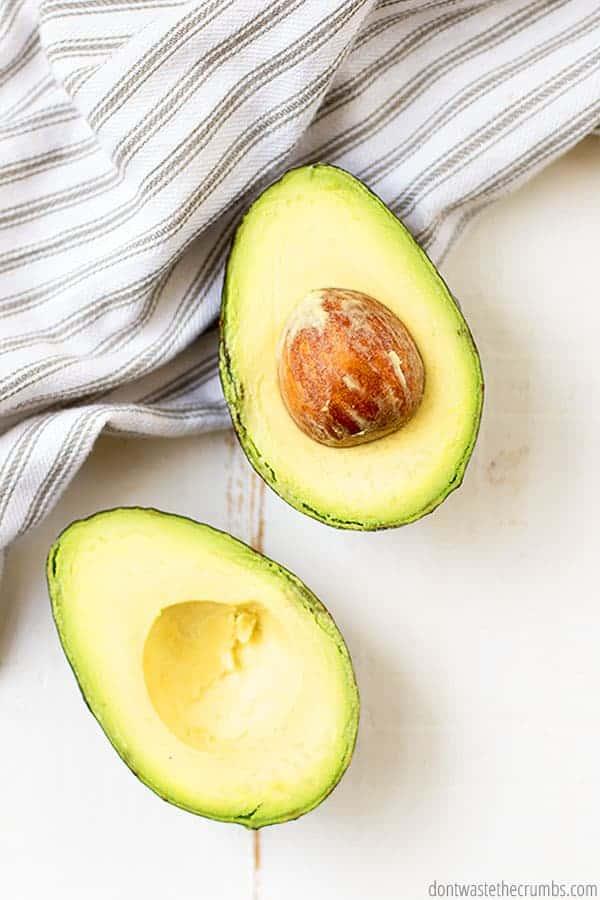 A ripe avocado is sliced in half.