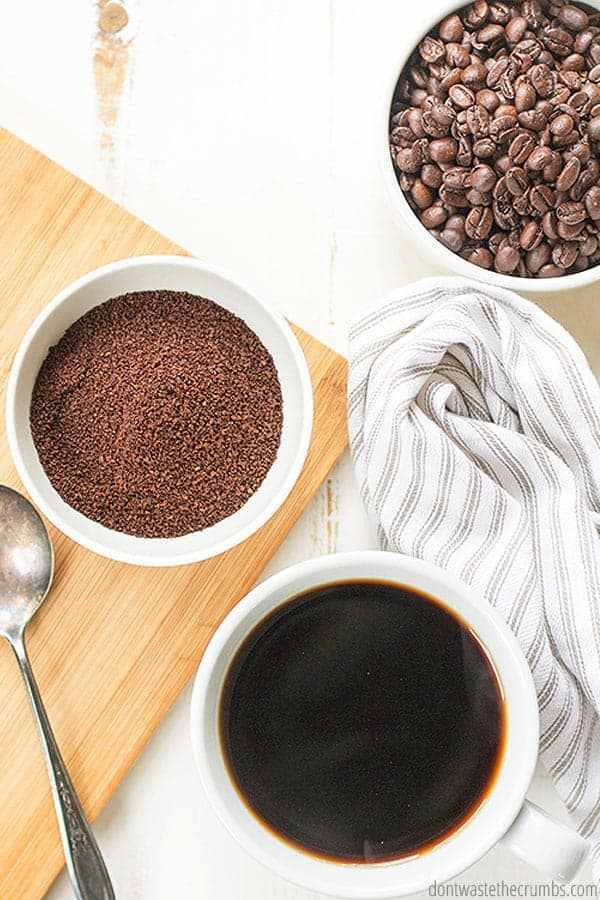 A cup of brewed coffee sits next to a small bowl each of ground and whole bean coffee.