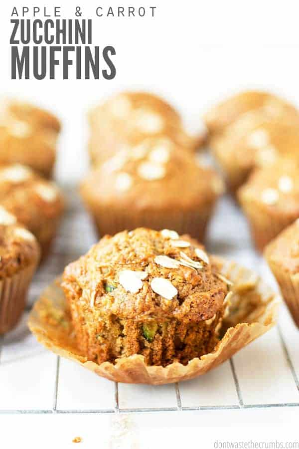 Carrot zucchini muffins rest on a baking rack. The muffins, a rich orange color, are dusted with oats on top.
