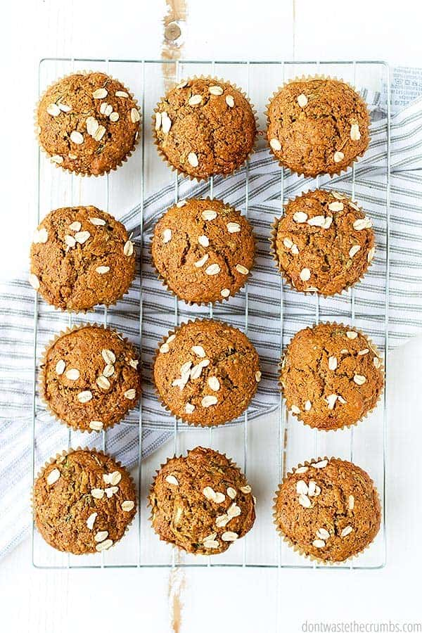 Muffins are sprinkled with oats and cool on a baking rack.