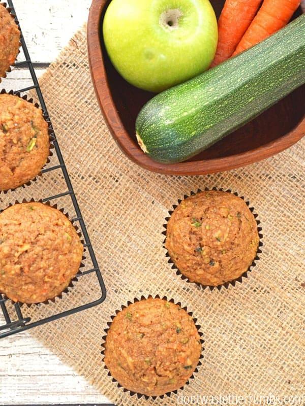 Baked muffins sit next to a bowl filled with an apple, a zuchhini, and two carrots.