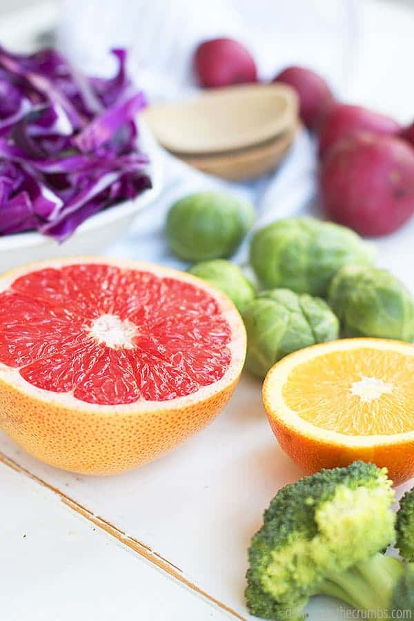 Fresh halved grapefruit and oranges sit next to brussel sprouts, red potatoes, broccoli, and red cabbage.
