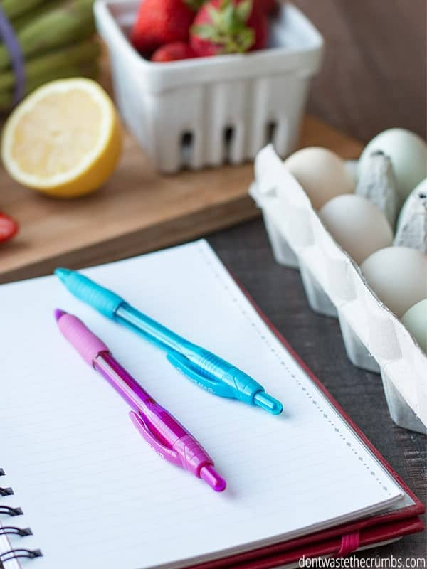 A notepad and pins sits next to a carton of eggs and a butcher block with fresh strawberries and a half lemon on it.